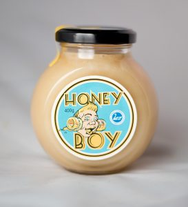 a Picture of a glass jar of honey on a white background with honeyboy face on blue label on the side of the jar