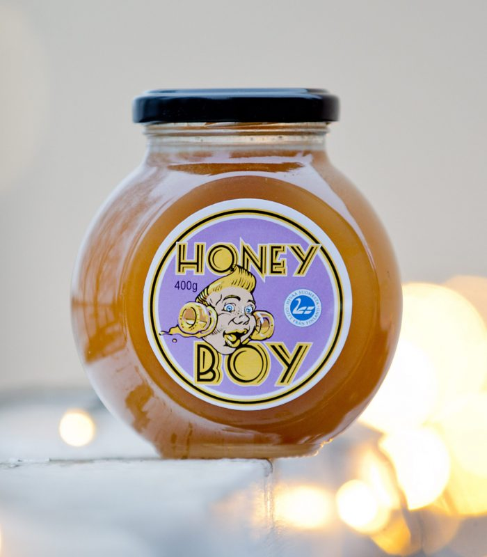 a Picture of a glass jar of honey on a white background with honeyboy face on purple label on the side of the jar